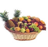 Arrangement of Fresh Fruits in a Huge cane basket. (Huge Basket with Apples, Grapes, Oranges, Chikoos and Pineapples).